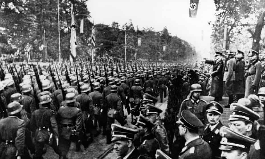 The rising storm: German troops parade in front of Hitler and his Nazi generals after entering Warsaw on 5 October 1939.