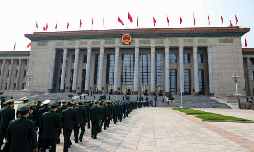 Soldiers and armed police walk into the Great Hall of the People in Beijing.