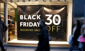 Shoppers walk past a store promoting Black Friday in London.