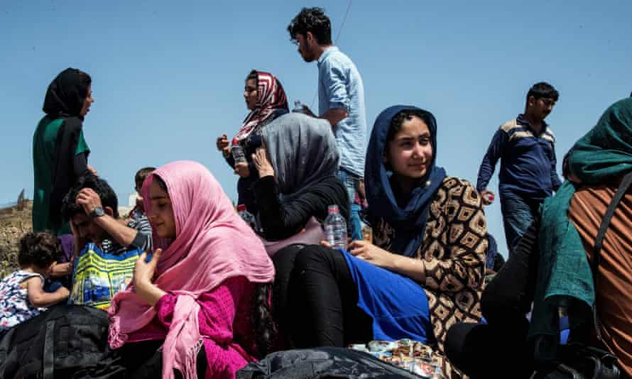 People sit near the village of Finokalia in Crete after arriving in a migrant boat on 31 May