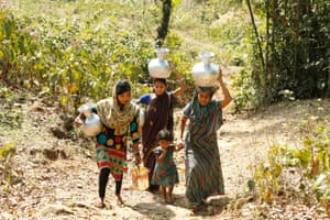 Women return home after collecting drinking water from a ringwell at the Sreepur tea estate, Sylhet. They have to cross a dangerous highway to reach the water spot.