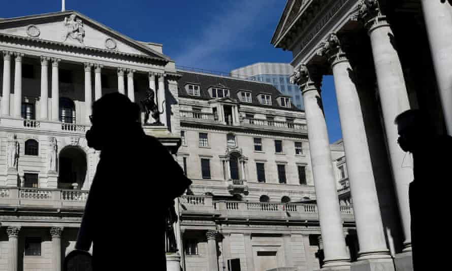 People wearing masks walk past the Bank of England