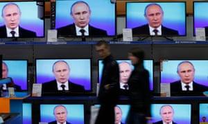 Visitors walk past TV sets in the Siberian city of Krasnoyarsk during Putin's live nationwide phone-in