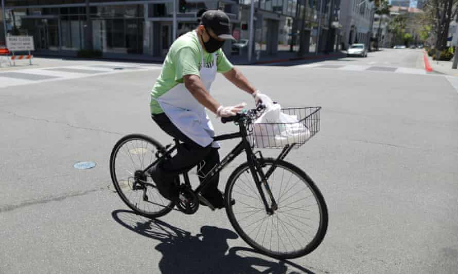 A food delivery driver cycles on an empty road in Beverly Hills, California.