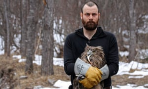 Jonathan Slaght in snowy forest wearing gauntlets and holding a Blakiston's fish owl