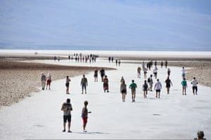 Around 60 people walking on salt flats in Badwater in Death Valley