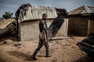 A police officer patrols an area of destroyed and burned houses after a recent Fulani attack in the Adara farmers' village of Angwan Aku