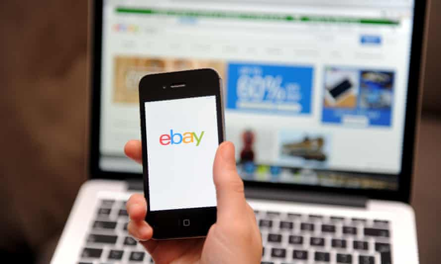 A person using eBay on a mobile phone and laptop