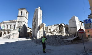 A firefighter stands in front of the destroyed basilica of San Benedetto in the historic centre of Norcia one day after the quake hit.
