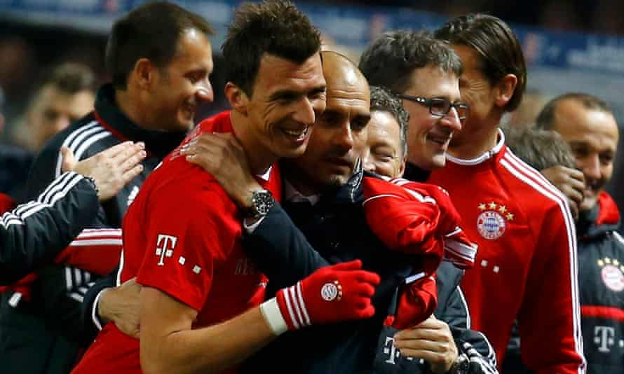 Guardiola celebrates with Mario Mandzukic after Bayern's 19th straight Bundesliga victory sealed the 2013-14 title.