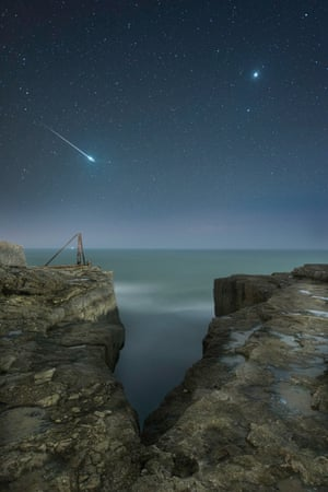 Shooting Star and JupiterRob Bowes (UK). A shooting star flashes across the sky over the craggy landscape of Portland, Dorset, as our neighbouring planet Venus looks on. The image is of two stacked exposures: one for the sky and one for the rocks