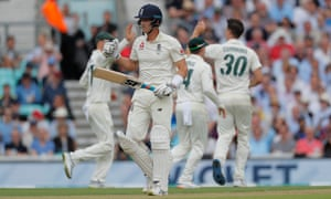 England's Joe Denly trudges off as Australia's Pat Cummins celebrates taking his wicket.