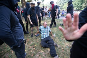 A knocked-down man being protected by counter-protesters.