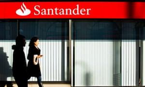 People walking past a Santander bank
