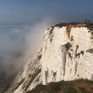 People stand on a cliff at Beachy Head amidst mist, near Eastbourne.