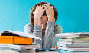 Teacher in classroom head in hands
