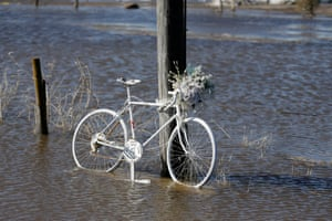 A painted bicycle sits in flood water in Waterloo, Neb., Wednesday, March 13, 2019. Forecasters say major flooding is likely in eastern Nebraska and western Iowa over the next couple days and some rural roads already had to be closed after being covered with water. The National Weather Service says this week's significant rain is especially problematic because much of the region is still covered by a blanket of snow and the ground is still frozen, so the rail flows right into streams and rivers.