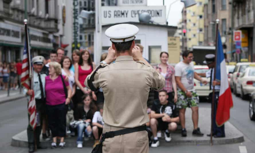 An actor dressed as a US military police officer photographs a group of tourists at Checkpoint Charlie in Berlin.