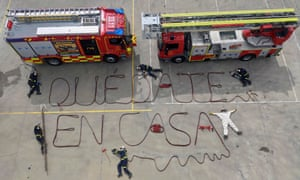 Firefighters perform an action and write the message 'Stay at Home', with their fire hoses in the town outside Madrid, Spain