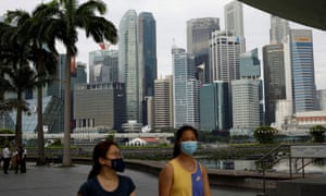 People wearing face mask pass the city skyline during the coronavirus outbreak, in Singapore.