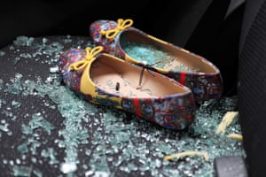 Shattered glass covers shoes left on the seat of a car damaged after a rocket attack in Tel Aviv, Israel