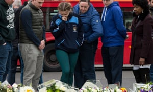 People look at a floral tribute to PC Keith Palmer outside the Palace of Westminster.