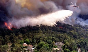 A heavy lift helicopter drops water on a bushfire threatening homes in the northern suburbs of Sydney.