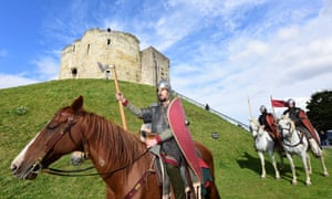 Members of King Harold's army ride past Clifford's Tower in York