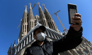 A tourist wearing a protective mask takes a selfie outside the Sagrada Familia in Barcelona.