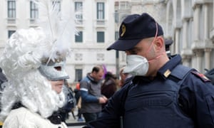 A police officer wearing a protective face mask stands next to a masked carnival reveller at Venice Carnival, which the last two days of, as well as Sunday night's festivities, have been cancelled because of an outbreak of coronavirus, in Venice, Italy February 23, 2020. REUTERS/Manuel Silvestri