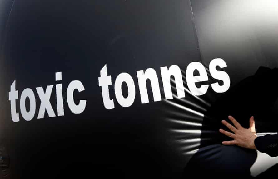 A climate activist pushing a giant ball bearing the words 'toxic tonnes' during a protest outside the European parliament in Brussels in 2015