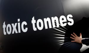 "An environmental activist pushes a giant ball with the words, ""toxic tonnes"" during a protest over carbon pricing reforms outside the European Parliament in Brussels"