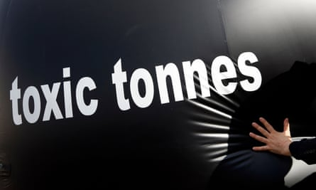 Environmental activist pushes a giant ball with the words, Toxic tonnes