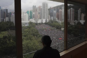 A person stands near a window overlooking a protest in Victoria Park, Hong Kong.