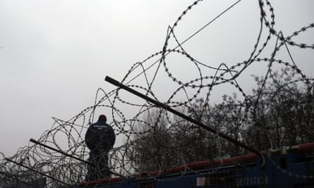 A Hungarian police officer stands guard at Serbia's border with Hungary near a makeshift camp in Horgos in February.