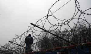 A Hungarian police officer stands guard at the border with Serbia.