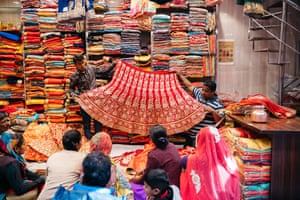 Two men hold out a piece of textile in front of a group of customers in Jaipur, India.