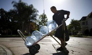 A Sparkletts bottled water delivery worker carries water to homes in Los Angeles.