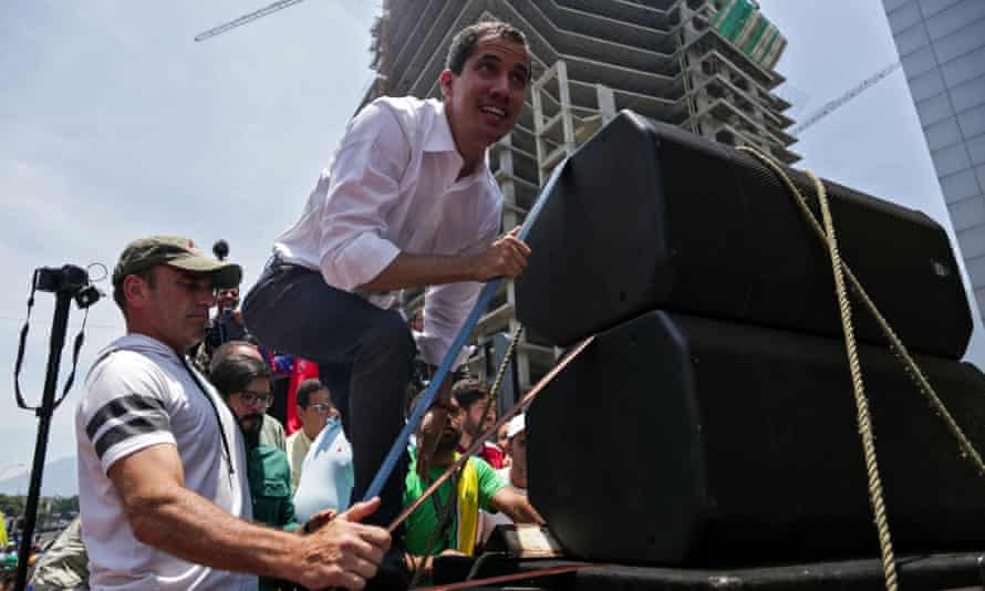 Juan Guaidó climbs up a makeshift stage during a rally to commemorate May Day in Caracas.