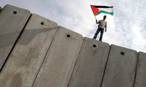 A Palestinian man stands on the controversial Israeli barrier and waves a Palestinian Flag near Jerusalem