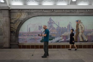 A tourist takes a photo during a visit to a subway station in Pyongyang, North Korea