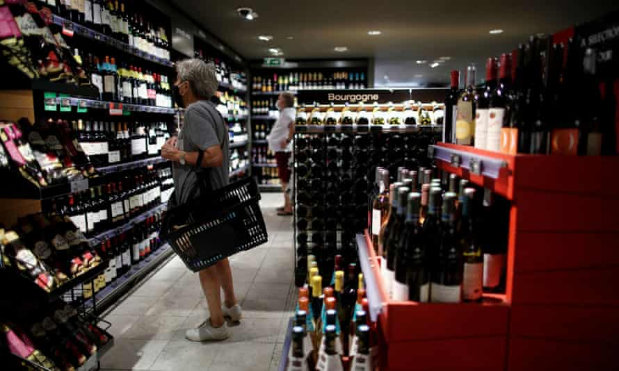 A customer browses bottles of wine for sale inside a Monoprix supermarket operated by Casino Group, in Paris