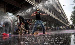 Protesters throw pink paint toward the police while being sprayed with water cannon in Bangkok.
