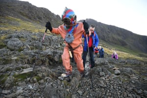 A man in a diving suit climbs Scafell Pike in England's Lake District