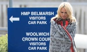 Pamela Anderson outside Belmarsh  prison wearing a cloak emblazoned with slogans