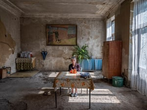 An elderly lady sitting at a table