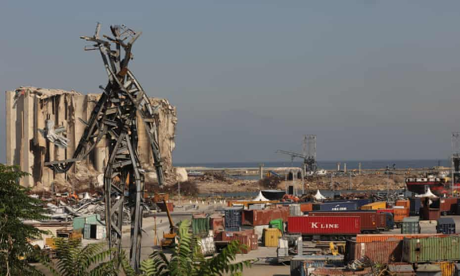 The port of Beirut and the memorial sculpture of a giant angular figure made from the wreckage of last summer's blast.