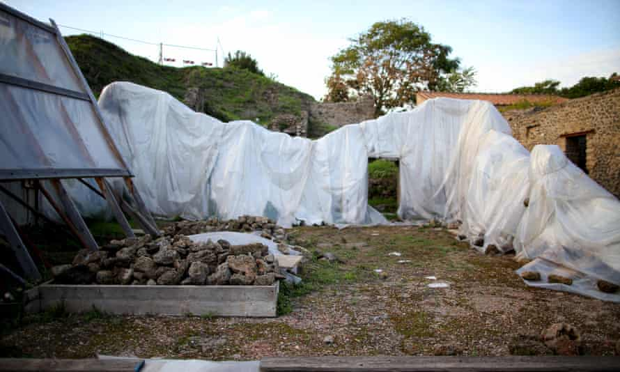 Plastic sheets cover the remains of a house in Pompeii.