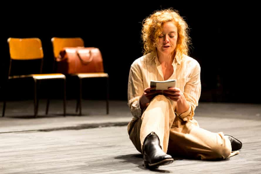 A woman sits on a wooden floor reading a book