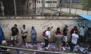 Voters wait in line outside a polling station in Rio's Maré favela